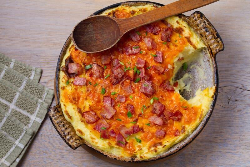Cocotte en terre par cheddar de purée de pommes de terre avec le lard Cocotte en terre cuite au four de pomme de terre de cheddar photo libre de droits