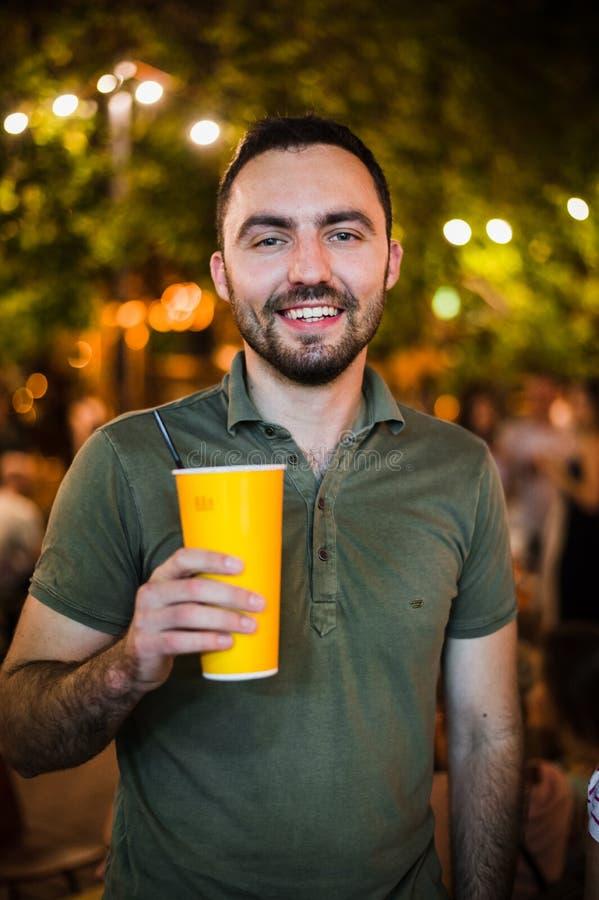 Coctail или пиво красивого человека выпивая на партии вечера ночи парка улицы стоковое фото rf