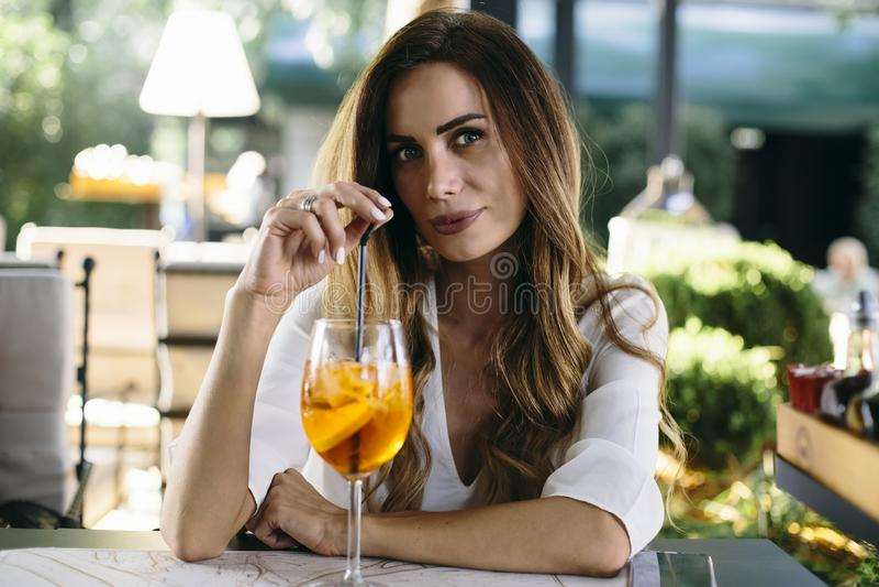 Coctail привлекательной молодой женщины выпивая в кафе внешнем стоковая фотография rf