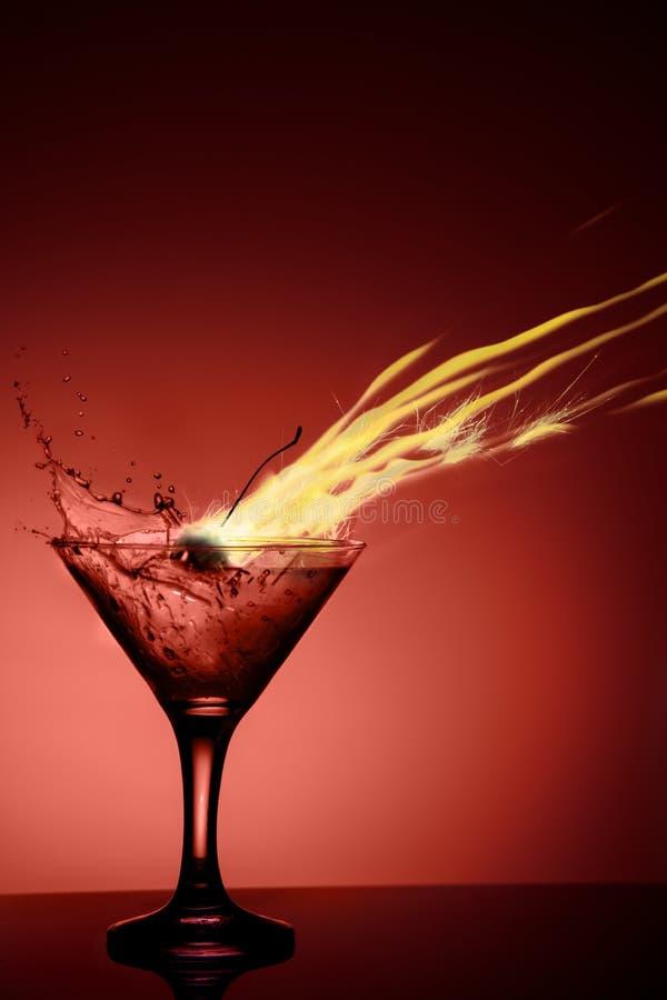 Coctail alcolico con una fiamma e una spruzzata su fondo rosso fotografia stock libera da diritti