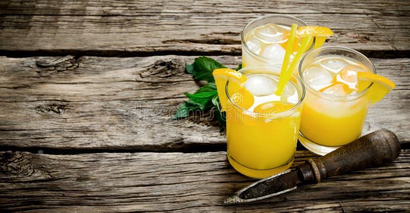 Coctail av nya apelsiner med is och sugrör arkivfoton