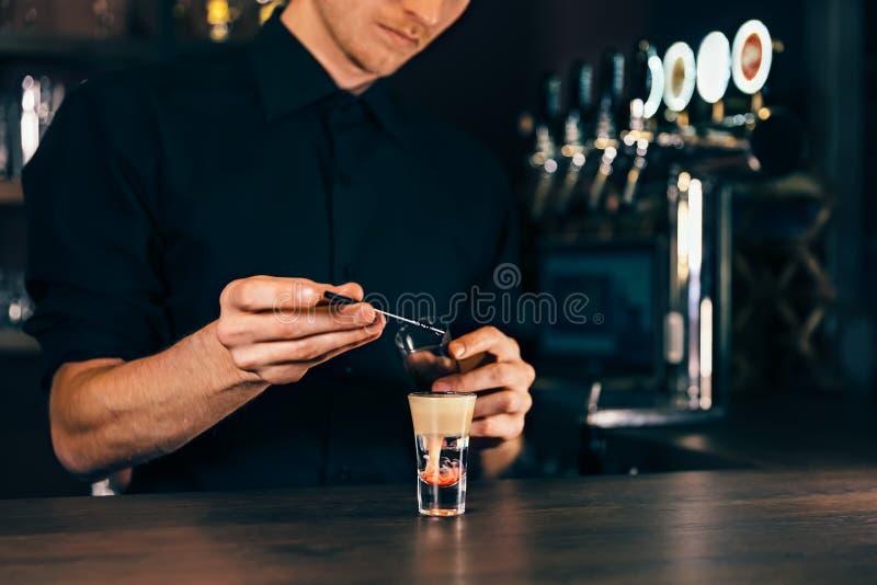 Coctail för bartenderdanandealkohol i restaurang Den sakkunniga bartendern tillfogar ingredienscoctailen på nattklubben royaltyfri bild