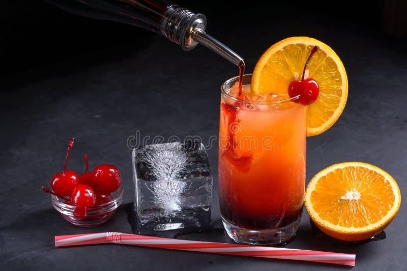 Coctail för danandetequilasoluppgång Granatäppelsaft hällde långsamt in i ett exponeringsglas av is, orange fruktsaft och tequila royaltyfri foto
