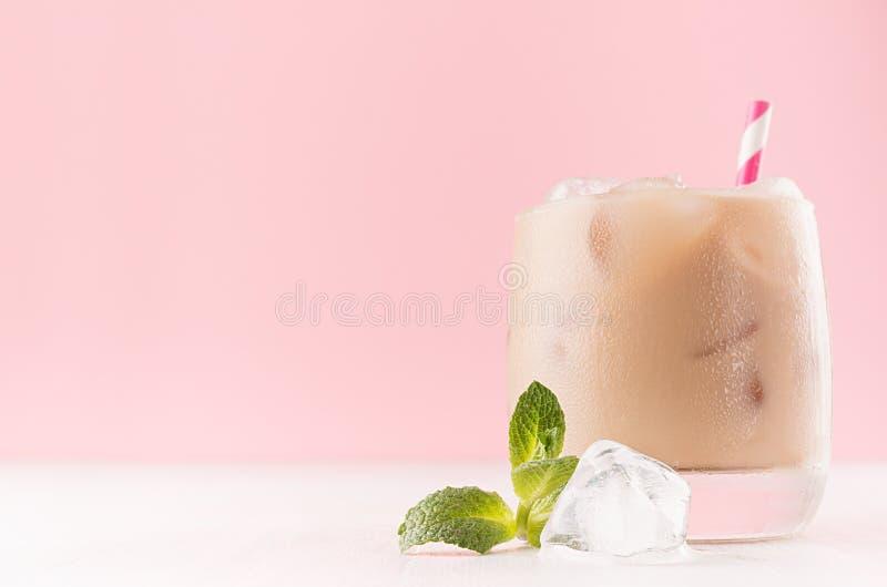Coctail för med is kaffe för sommar alkoholiserad med iskuber, den gröna mintkaramellen, randigt sugrör på mjukt ljus - rosa arkivbild