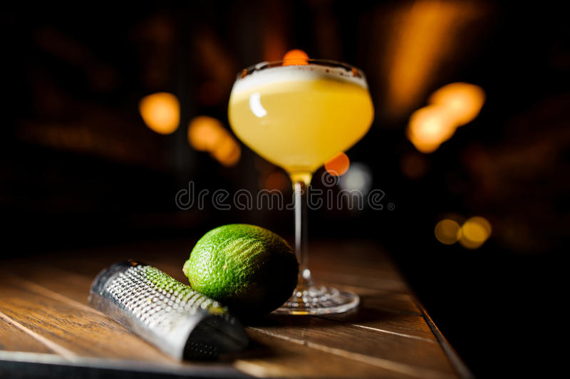 Coctail and lime on the brown table. Coctail and lime on the brown wooden table stock image