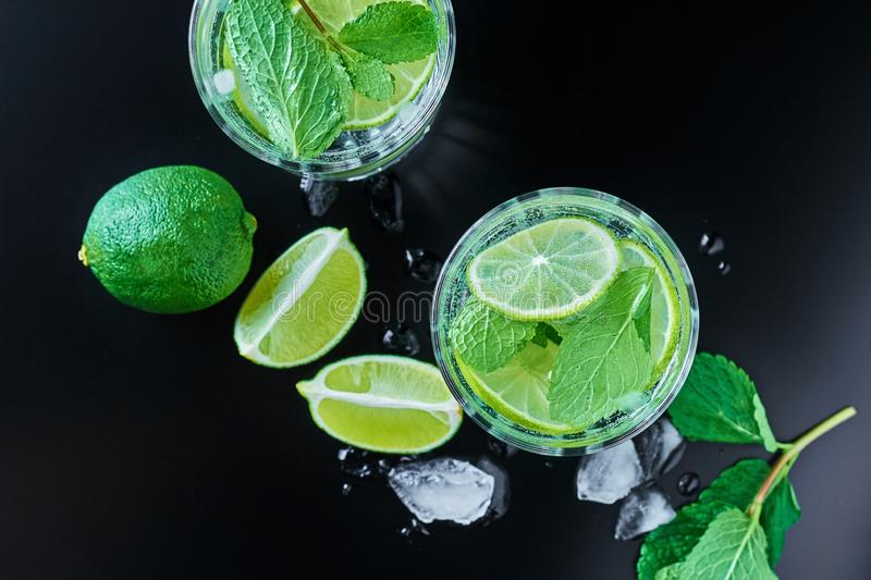 Coctail with lime and mint on dark background. Two glasses of mint coctail with lime on dark background, top view stock photo