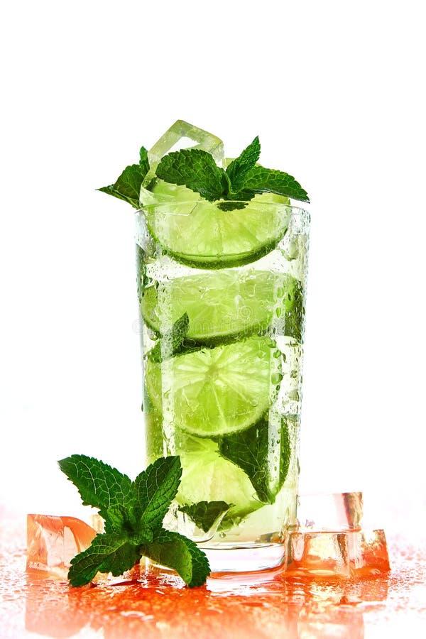 Coctail med limefrukt, is och mintkaramellen på vit bakgrund arkivfoton