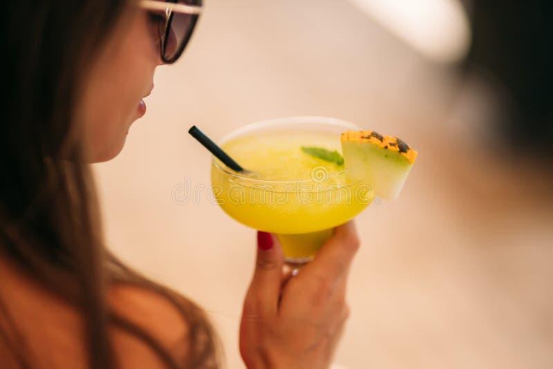 Coctail na m?o da mulher na praia Coctail amarelo com mel?o fotografia de stock royalty free