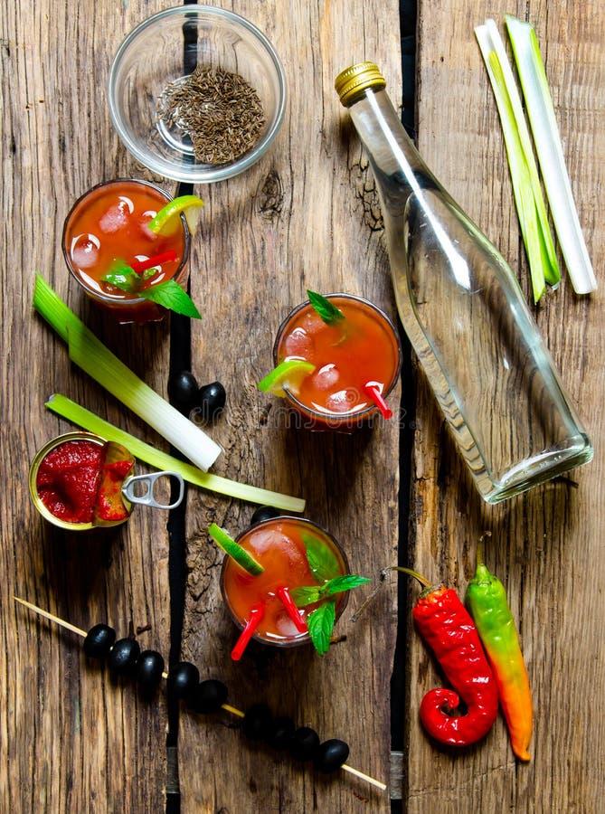Coctail tre med ingredienser - is, tomater, vodka, selleri, peppar, oliv och mintkaramellsidor på en trätabell royaltyfria foton