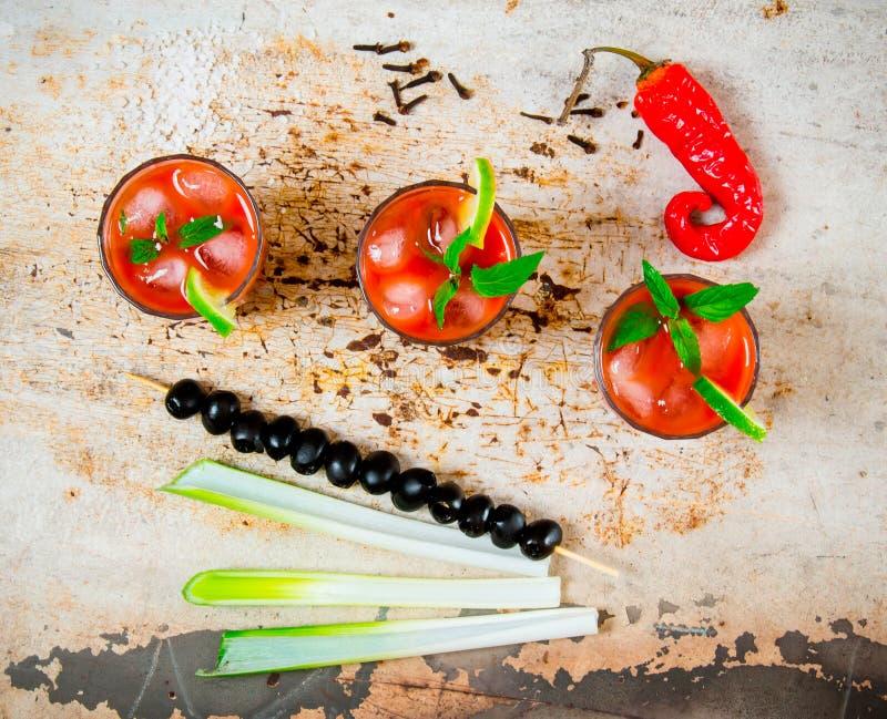 Coctailar som göras av tomater, vodka, is, limefrukt, peppar, saltar och mellanmålet med selleri och svarta oliv på lantlig bakgr royaltyfri foto