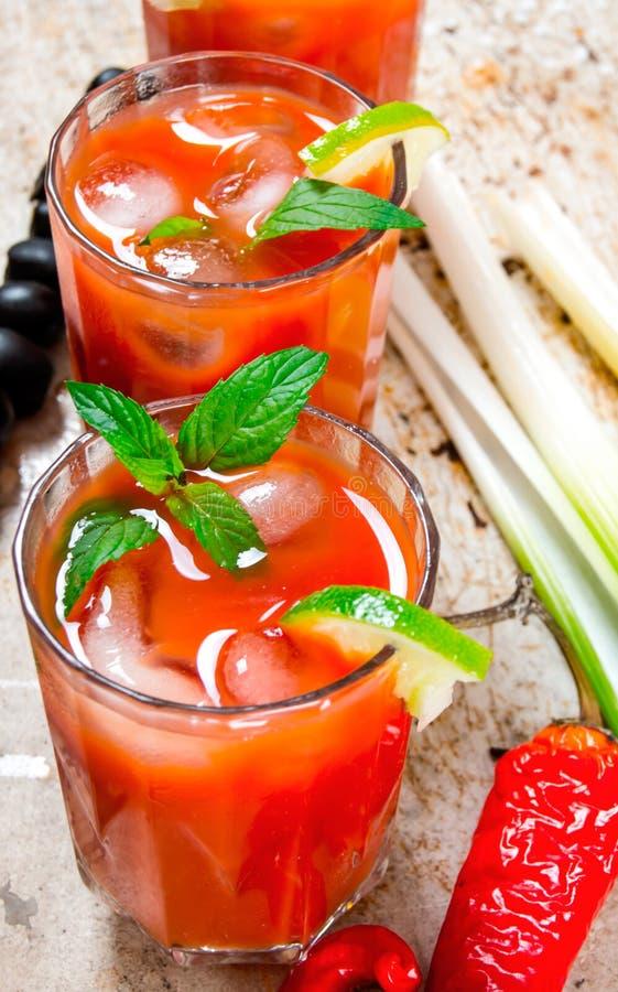 Coctailar som göras av tomater, vodka, is, limefrukt, peppar, saltar och mellanmålet med selleri och svarta oliv på lantlig bakgr royaltyfria bilder