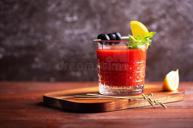 CoctailBloody Mary med is, saltar och mellanmål i exponeringsglas på en trätabell royaltyfria foton