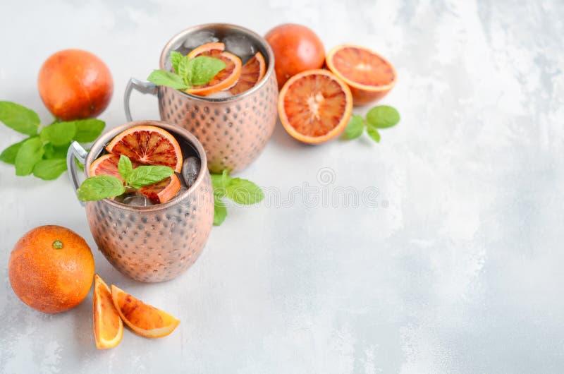 Coctailen för alkohol för blodapelsinMoskvamulan med sidor och is för ny mintkaramell i koppar rånar på en grå konkret bakgrund royaltyfri bild