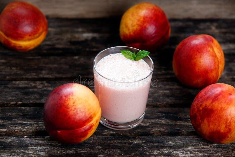 Coctailen från grekisk yoghurt och den nya saftiga nektarinen bär frukt close upp på den gamla trätabellen Bakgrund Utvalt fokuse arkivbild