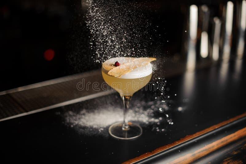 Coctailen i exponeringsglaset dekorerade med en torkad ananas och steg knoppen under sockerpulvret arkivbilder