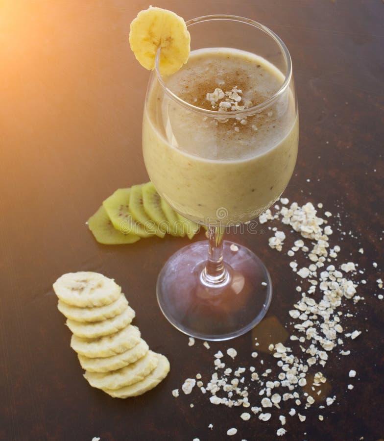 Coctailen med kiwin och bananen på en svart bakgrund, havremjöl, tonade vegetarian royaltyfri bild