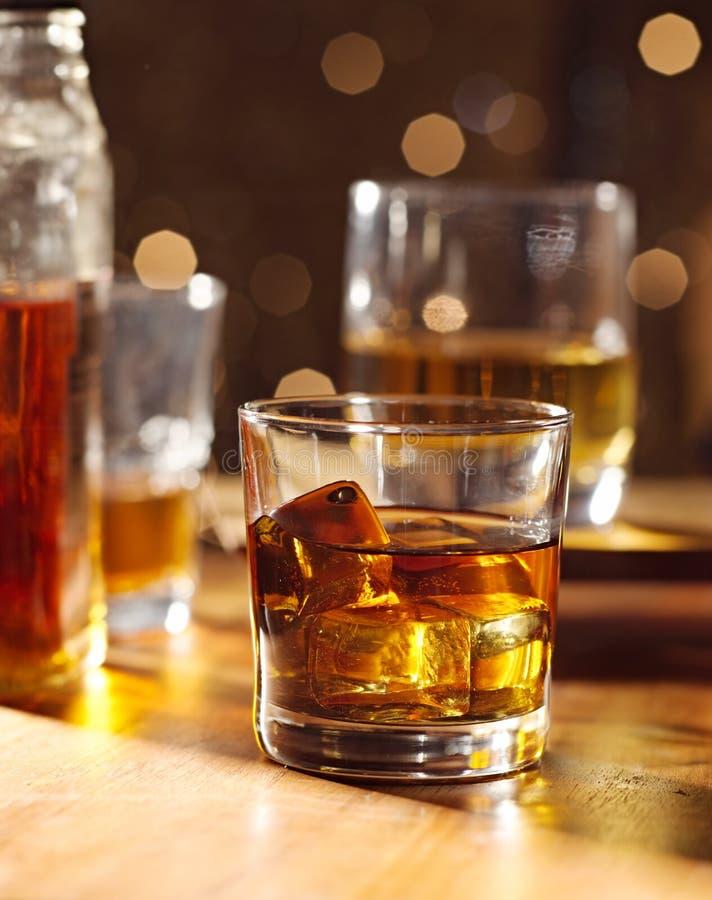 Coctailexponeringsglas av whiskey på trä bommar för arkivbilder