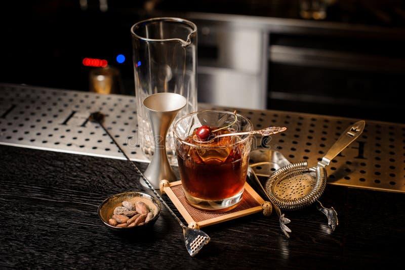 Coctailexponeringsglas fyllde med den starka och söta sommarcoctailen som dekorerades med den nya körsbäret på den mycket lilla s arkivbilder