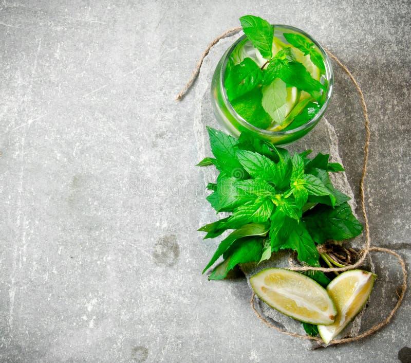 Coctailexponeringsglas - mintkaramell, is, rom och limefrukt på en stensockel arkivfoton