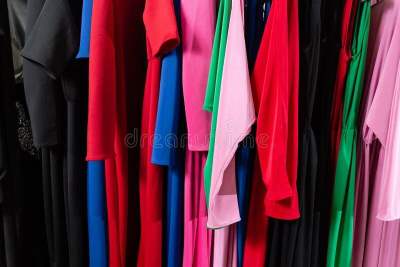 Coctailkl?nning Kl?der p? h?ngare p? det modernt shoppar boutique Ljusa m arkivbilder