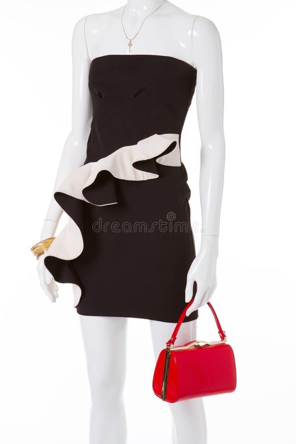 Coctailsvartklänning med den röda handväskan arkivbilder