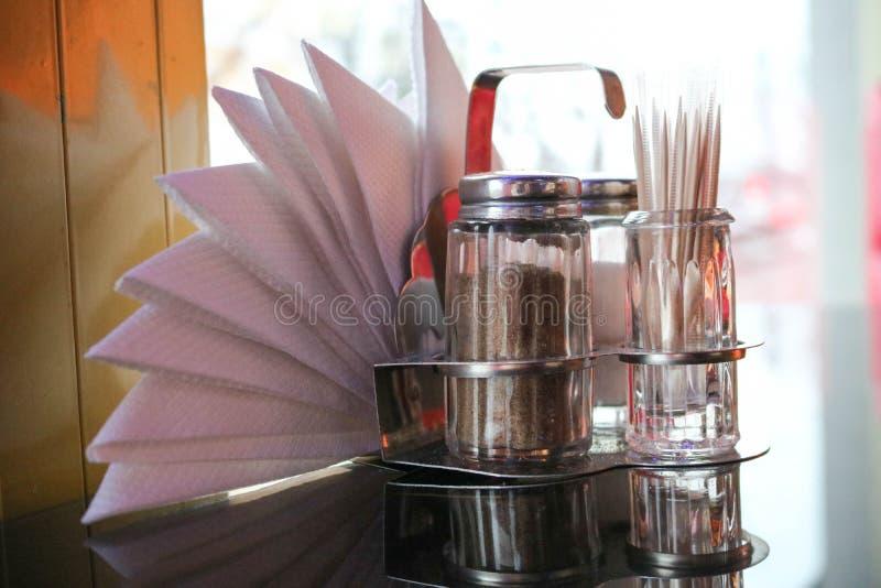 Coctelera de la pimienta y de sal, palillos y servilletas en la tabla en el café delante de la ventana por la tarde fotografía de archivo
