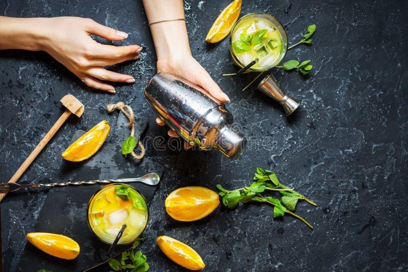 Coctelera del control de la mano de la mujer Cóctel alcohólico frío de la fruta cítrica del verano con la naranja y la menta en v imágenes de archivo libres de regalías