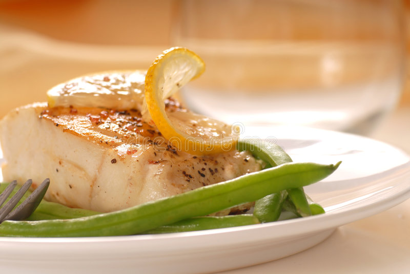 Cod fillet with green beans. Fresh sauteed cod fillet with green beans and lemon royalty free stock image