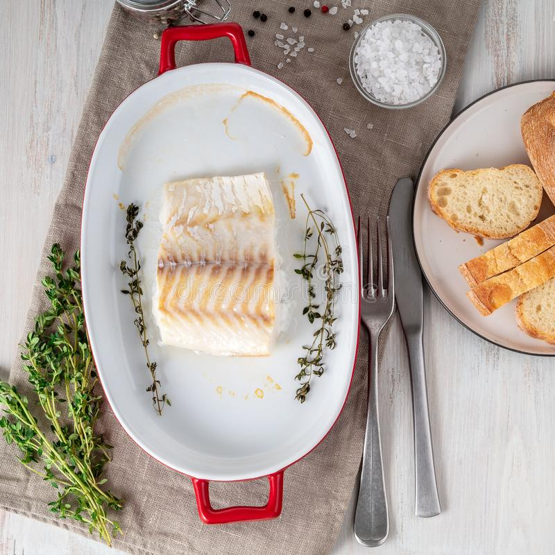 cod fish fillet, freshly cooked in oven with thyme in a porcelain dish for baking, bread on a plate, salt and pepper, white royalty free stock images