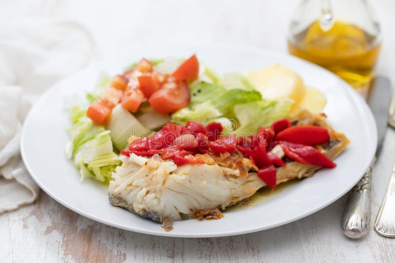 Cod fish with red pepper, potato and salad on white plate royalty free stock images
