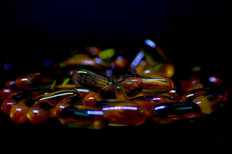 Cod liver oil omega 3 vitamin e gel capsules isolated on Black background stock images