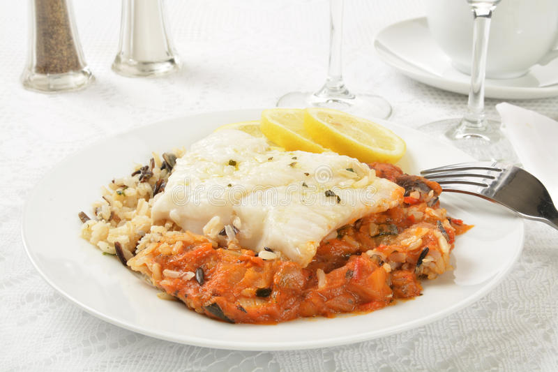 Cod Provencal on Rice. Cod provencale on wild rice with Ratatouille and lemon royalty free stock images
