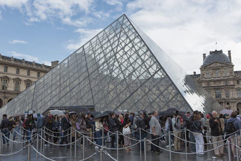 Coda dei turisti a He piramide del Louvre fotografia stock libera da diritti