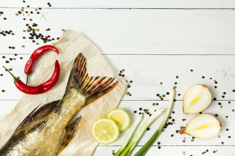 Coda del pesce fresco con le spezie su una tavola di legno bianca Cipolla verde, peperone e limone giallo Spazio per testo immagine stock