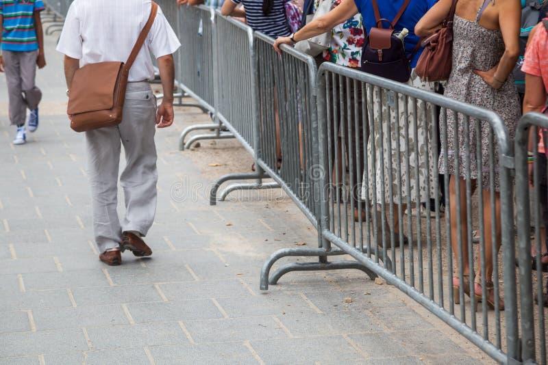 Coda della gente dietro una barriera fotografie stock libere da diritti
