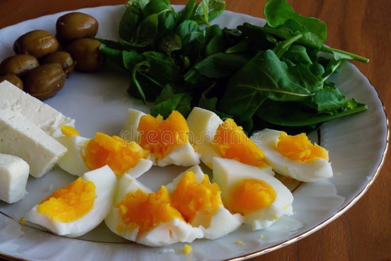 Coddled熟蛋用在白色盘的季节草本乳酪和橄榄采取与自然光 图库摄影