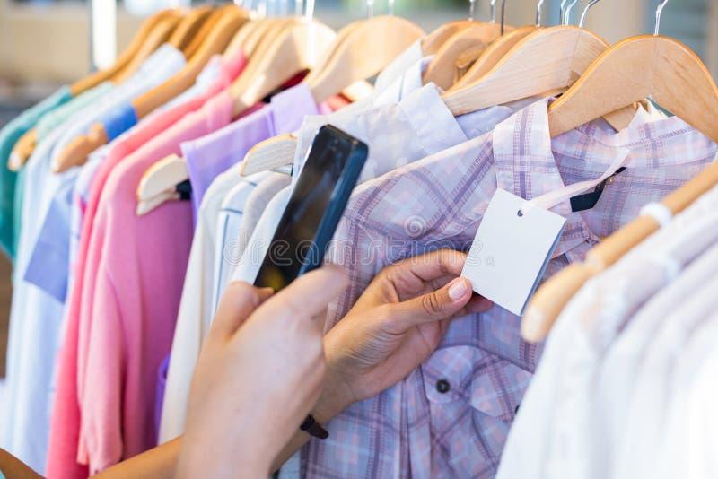 Code barres de balayage de femme avec son téléphone portable photos stock