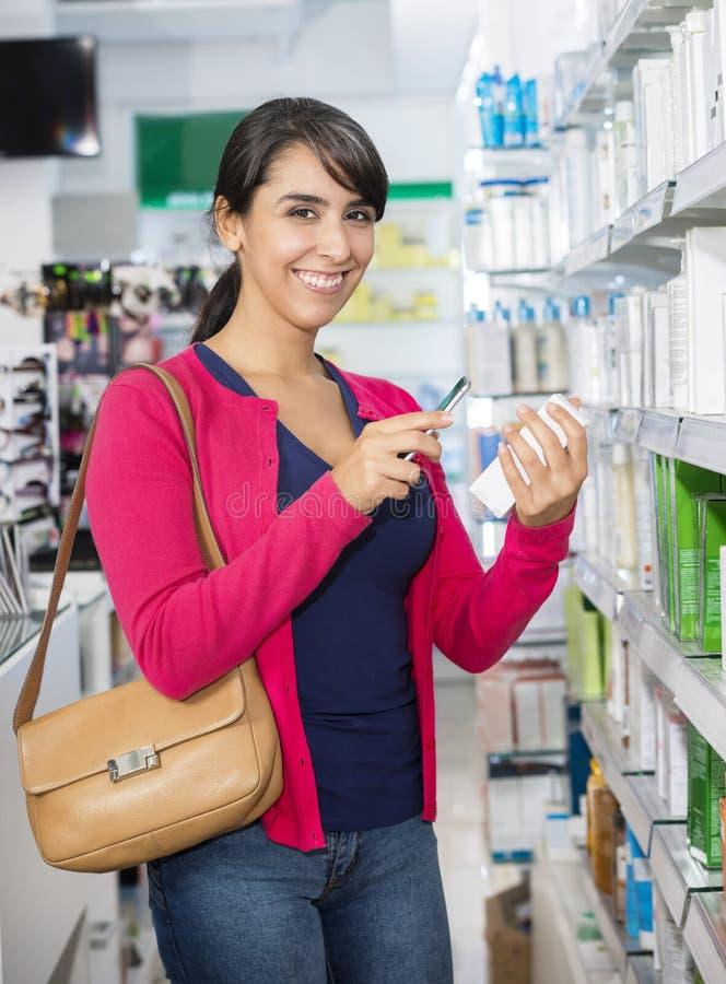 Code barres de balayage de femme par le téléphone intelligent dans la pharmacie photos libres de droits