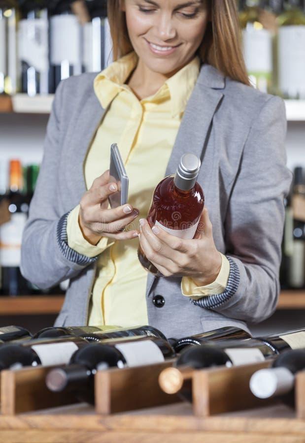 Code barres de balayage de femme sur la bouteille de vin avec le téléphone portable images libres de droits