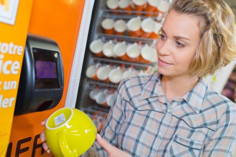 Code barres de balayage de femme sur le produit au magasin de matériel photo libre de droits
