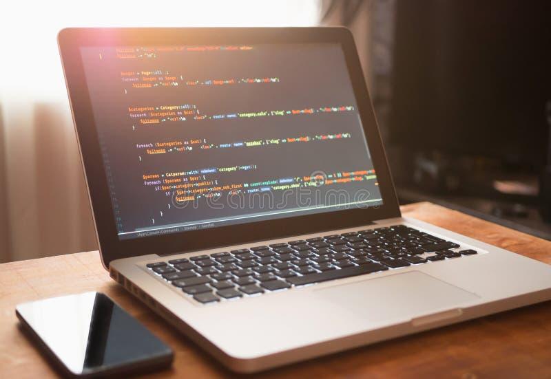 Code informatique sur se développer et téléphone portable de Web d'ordinateur portable photo libre de droits