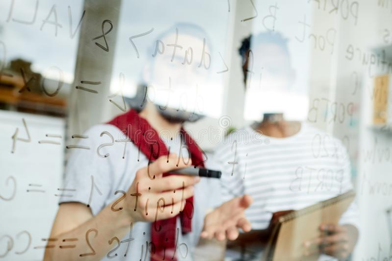 Code notes on board. One of programmers pointing at software codes on board during discussion with colleague royalty free stock photos