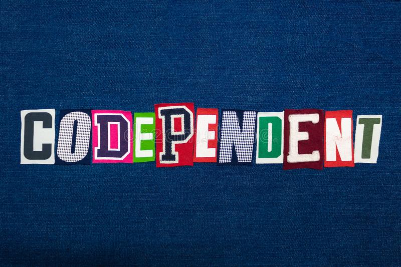 CODEPENDENT word text collage, multi colored fabric on blue denim, mental health concept. Horizontal aspect royalty free stock image