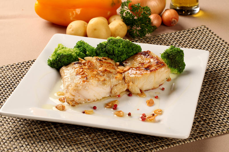 Codfish - fish fillet in sauce with garlic and vegetables. Codfish - fish fillet in sauce and vegetables stock photo