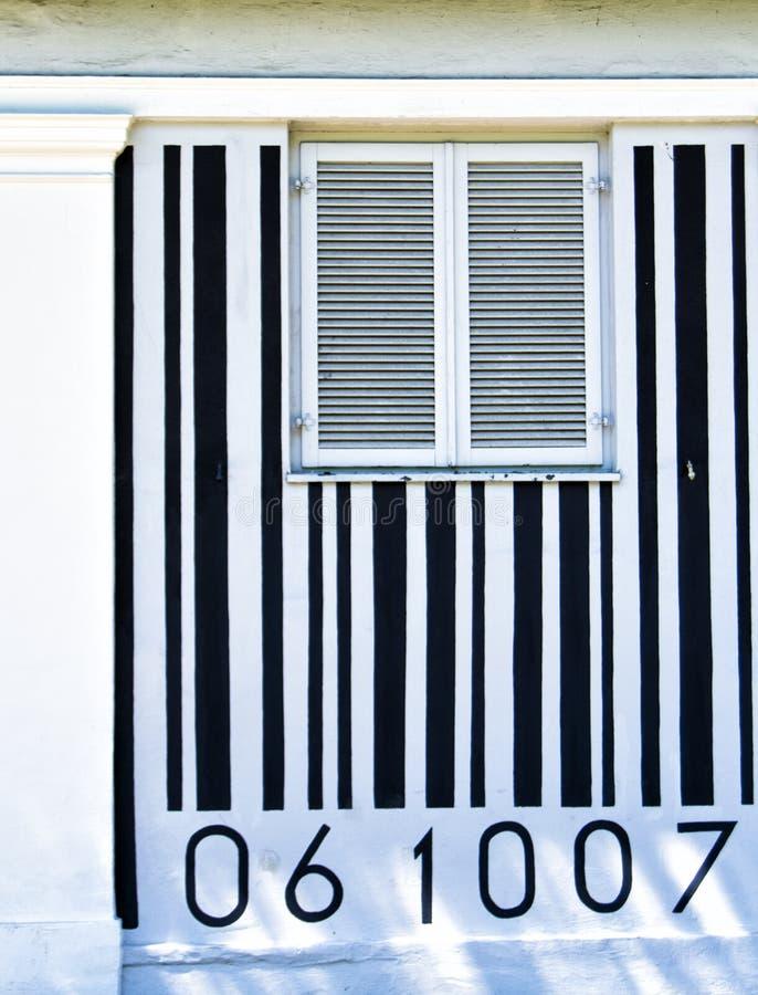 Codice a barre in bianco e nero dipinto su una parete della casa con una finestra nel mezzo fotografie stock libere da diritti