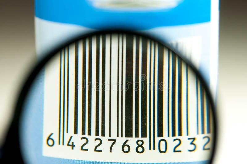 Codice a barre di carta graffiato sul prodotto usato tramite la lente d'ingrandimento immagine stock