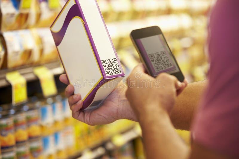 Codice del buono di esame dell'uomo in supermercato con il telefono cellulare immagini stock
