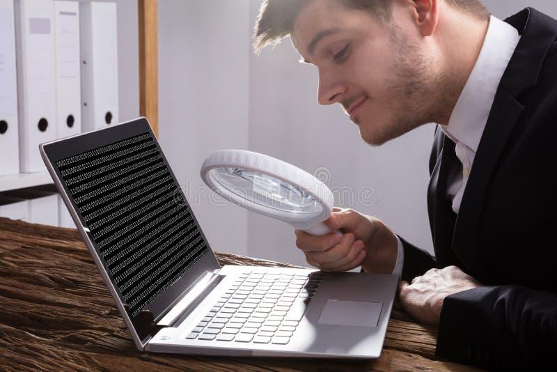 Codice di Looking At Binary dell'uomo d'affari con la lente d'ingrandimento fotografie stock