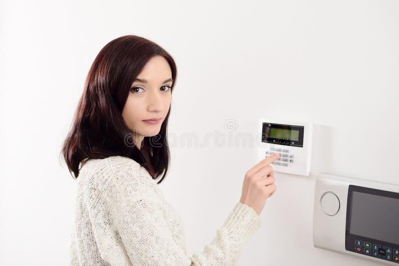 Codice entrante della donna sulla tastiera dell'allarme di sicurezza domestica fotografie stock