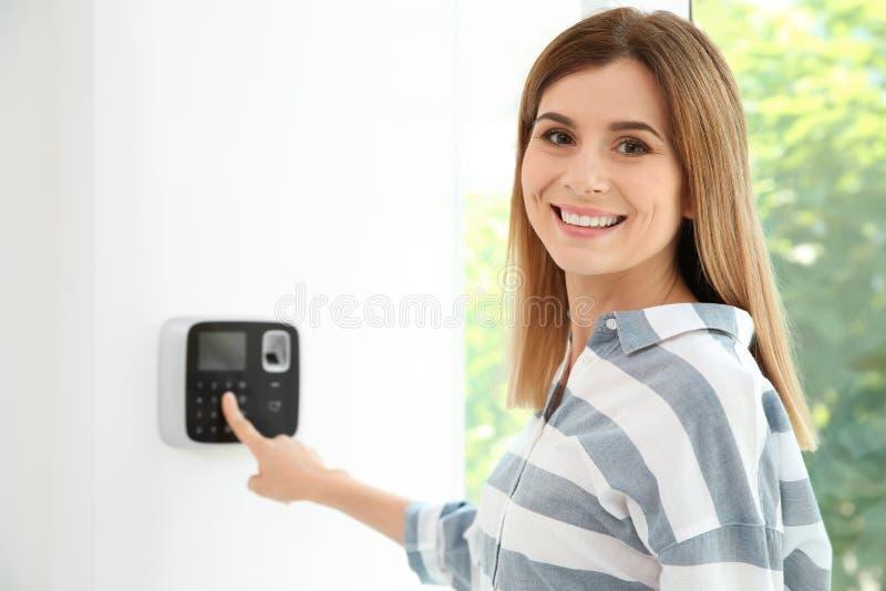 Codice entrante della giovane donna sul keypa del sistema di allarme fotografia stock